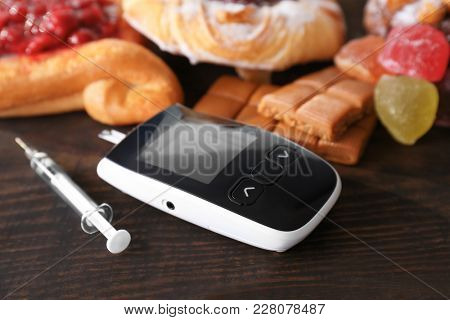 Digital glucometer, syringe and sweets on table. Diabetes diet