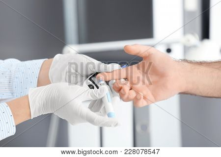 Doctor taking sample of diabetic patient's blood using lancet pen, closeup