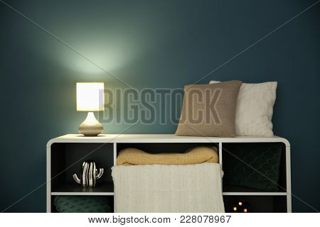 Shelving with stylish lamp in living room