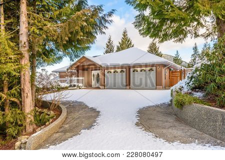 A typical american house in winter. Snow covered. Fantastic forest view.