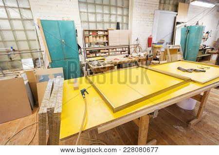 production, manufacture and woodworking industry concept - glue gun and frame on workbench at furniture factory workshop