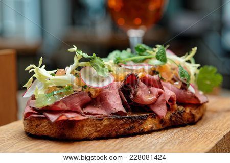 Sandwich with roast beef pastrami on restaurant table, close-up