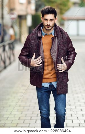 Attractive Young Man Walking In An Urban Road In Winter Clothes.