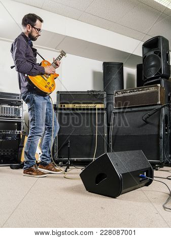 Photo Of A Man Playing His Electric Guitar In A Recording Studio In Front Of Amplifiers.
