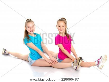 Lovely Girls Gymnasts Together Make A Twine. The Concept Of Sport, Fitness, Healthy Lifestyle. Isola