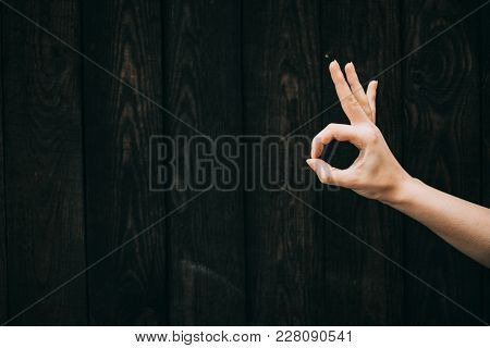Show Hand Okey On A Wooden Background