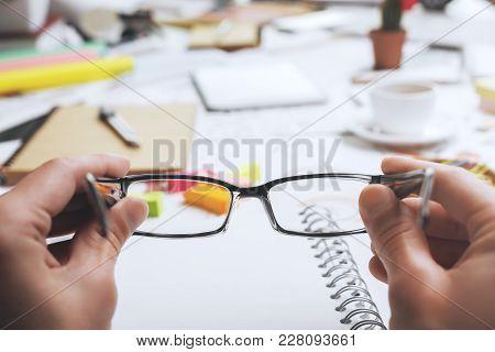 Male Hands Holding Glasses On Messy Office Desktop Background. Vision Concept