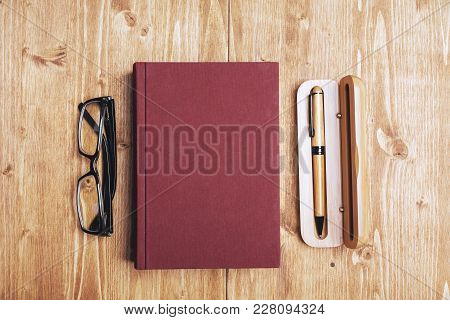 Close Up Of Wooden Desk With Book And Other Items. Education And Knowledge Concept