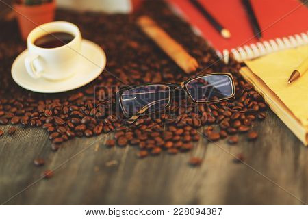 Close Up Of Wooden Table With Coffee Cup, Beans, Supplies And Other Items. Art, Hobby, Leisure, Morn