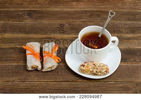 Cup Of Tea And Few Bar Of Muesli. Brown Wooden Background