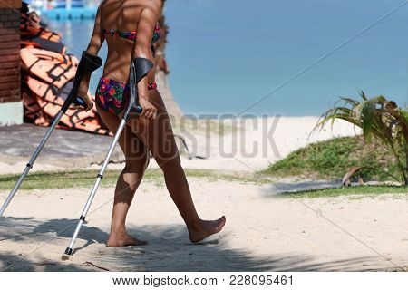 Injured Tourist With Crutch To Supporting Themself Relax On The Beach Summer In Thailand.
