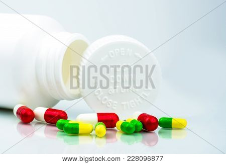 Colorful Pills On White Background And Plastic Bottle With Blank Label And Copy Space. Childproof Pa