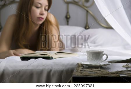 Young Beautiful Woman Reading Book On A Bed In Hotel Room.
