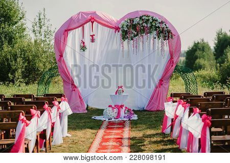 Wedding Arch For The Ceremony Decorated With White And Pink Fabric And Flowers