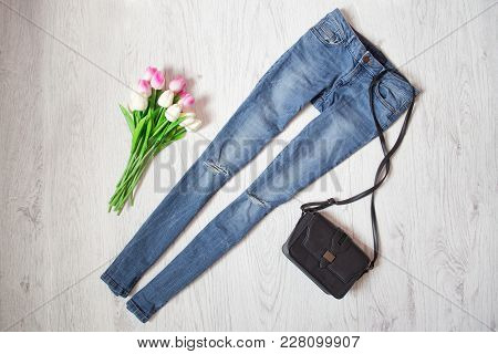 Blue Jeans, Black Handbag And Bouquet Of Tulips. Fashionable Concept