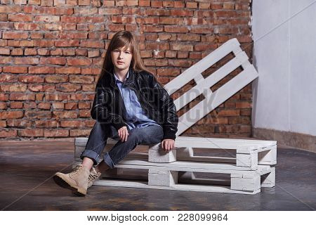 Girl Loft Interior.fashion Teen Girl. Stylish Mode Girl Sitting Pallets In Loft Interior. Girl Teen