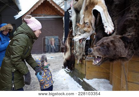 Russia, Moscow - February, 2018: Tourists in Russia, Woman and child looking at bear and wolf skin hanging for sale at Izmailovsky flea market in winter