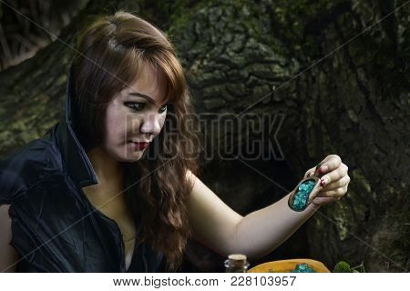 Young Witch From Legends And Fairy Tales Performs A Sorcerous Rite In The Forest