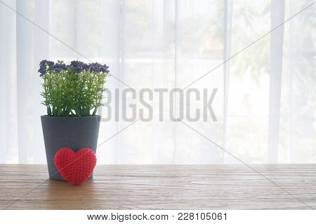 Wood Office Table With Violet  Flower Pot And Red Beautiful Knitted Fabric Heart Shape  On White Cur