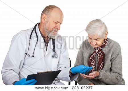 Mature Male Doctor Giving Pills To Disabled Old Woman On Isolated Background