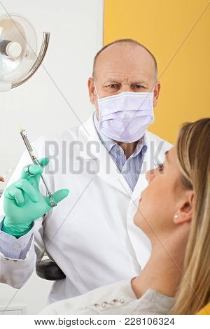 Dentist Holding Anesthetic Injection Preparing For Dental Treatment On Female Patient