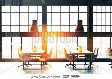 Loft Cafe Interior With A Concrete Floor, Black Framed Panoramic Windows And Wooden Tables With Chai