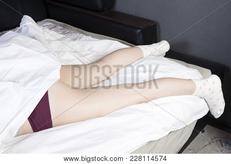 The Girl Is Sleeping Under A White Blanket, Her Legs In Socks Are Out Of The Duvet