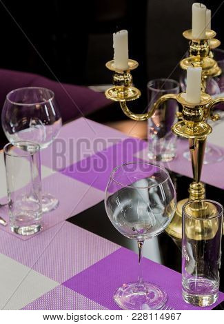 Glasses And A Candlestick On A Glass Table In A Restaurant. Romantic Setting.
