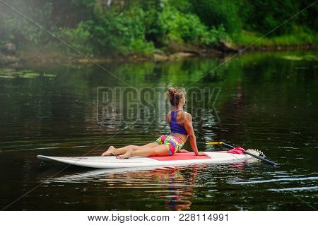 Young Athletic Woman Doing Fitness On A Board With An Oar On A Lake
