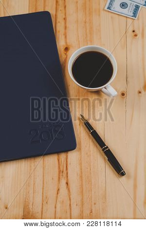 Personal Organizer Or Planner With Fountain Pen And Hot Coffee On Wood Table.