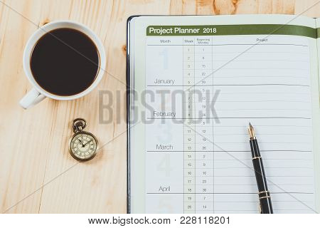 Personal Project Planner With Fountain Pen And Hot Coffee On Wood Table.