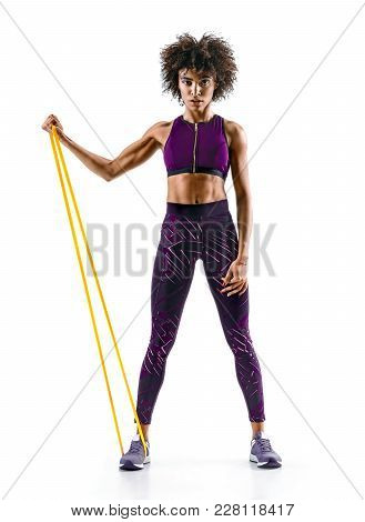 Strong Girl Using A Resistance Band In Her Exercise Routine. Young African Girl Performs Fitness Exe