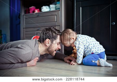 The Young Father Is Playing With His Little Daughter On The Floor In The Room. The Concept Of A Happ