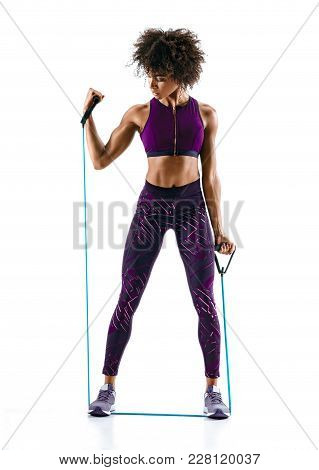 Athletic Girl Performs Exercises Using A Expander. Photo Of Young Girl Isolated On White Background.
