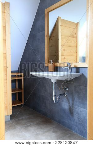 View Through Open Entrance To Bathroom. Wash Basin Mirror And Wooden Shelves In Modern Bathroom.