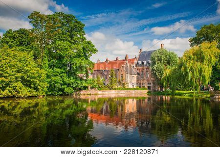Sunny Brugge Cityscape. Buildings Of Bruges Reflected In Lake. Historical Center Of Europe.