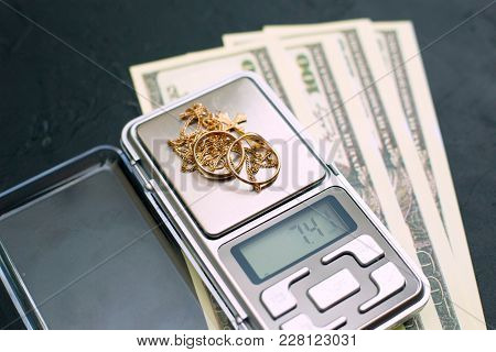 Gold Jewelry On The Scales And Money On A Black Background
