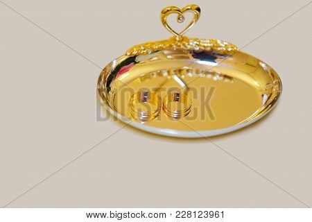 Wedding Rings On A Golden Tray. The Symbols Of Betrothal.