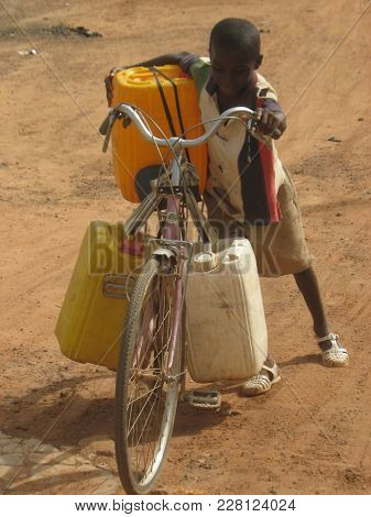 Ouagadougou/ Burkina Faso  - 7/20/2009: Unidentified Child Pushing Bike With Water Home.