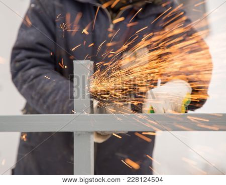 The Worker Cuts The Metal With Sparks .