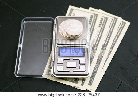 Silver Investment Coins On Jewelry Scales And Dollars On A Black Background