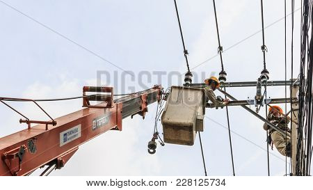 Bangkok, Thailand - August 5, 2017: Electrician Working On Electric Pole At An Altitude To Installs