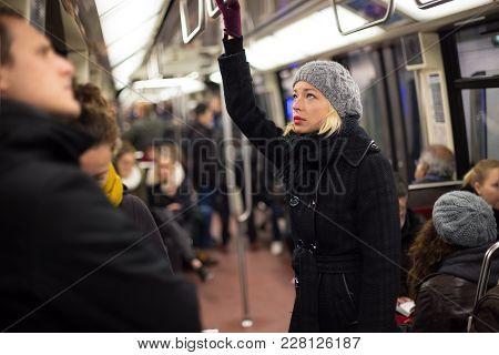 Beautiful Blonde Caucasian Lady Wearing Winter Coat Traveling By Metro In Rush Hour. Public Transpor