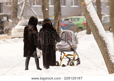 Mom And Grandmother With A Stroller In The Park .