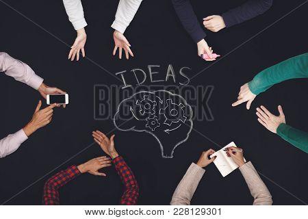 Teamwork Concept - Top View Of Six People Generate Ideasa. Blackboard Table.