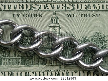 In Code We Trust. Blockchain Crypto Technology Principle. Real Metal Chain Is On Hundred Dollar Bank