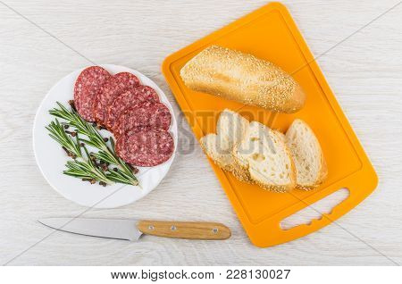 Pieces Of Smoked Sausage, Rosemary, Black Pepper And Carnation In Plate, Pieces Of Bread On Cutting