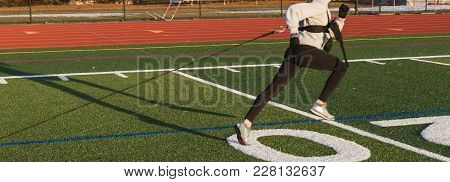 A Female High School Track Runner Is Sprinting With A Harness For Resistance Speed And Strength Trai