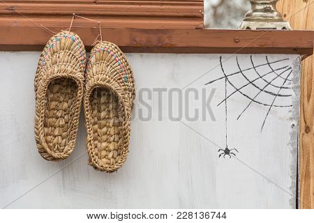 Wicker Shoes Hanging On A Nail On A Wall Furnace