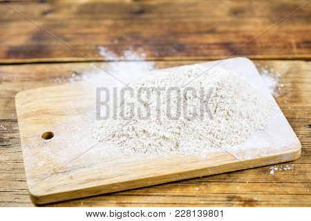 Close-up Heap With Rye Flour Coarse On A Wooden Board. Sie View